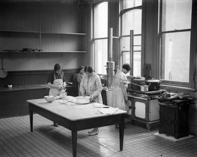 A kitchen with 4 women preparing a meal