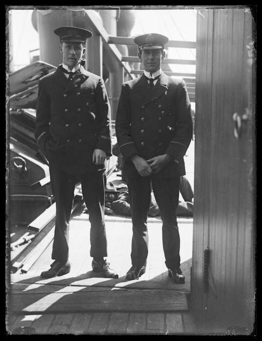 Two unidentified naval officers in uniform on board ship
