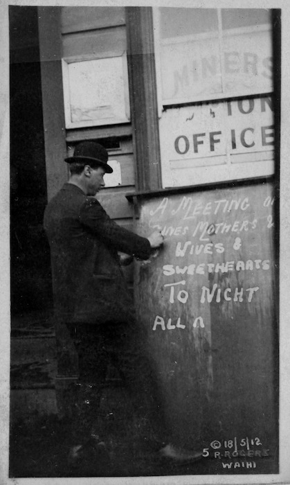 Man writing a sign announcing a meeting during the Waihi miners' strike