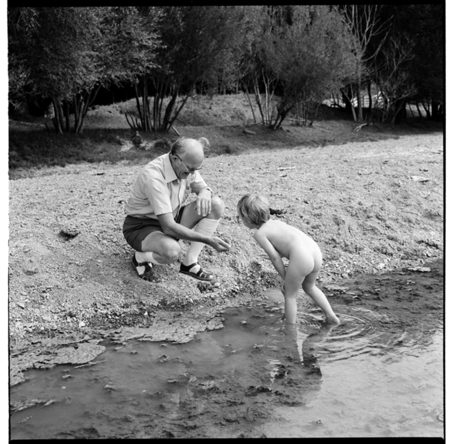 A child with grandfather [?] paddling in a stream