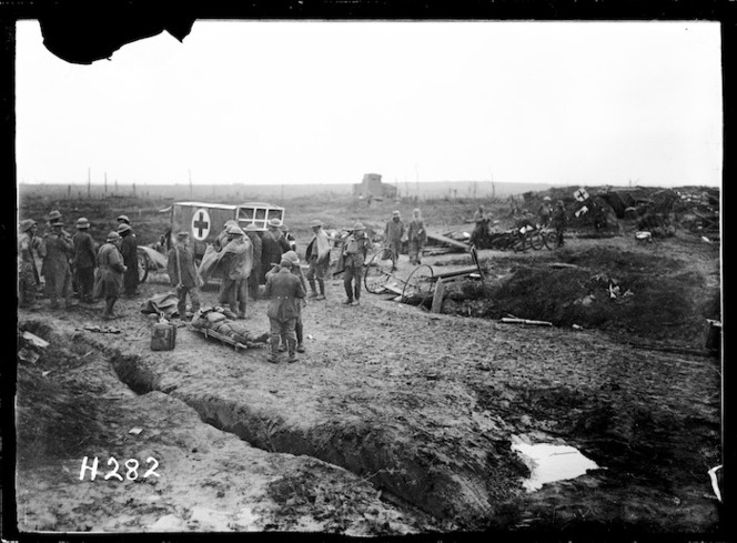 General view of an advanced dressing station on battleground at 'Somme Farm', Ypres Salient. Scene includes soldiers gathered around an ambulance and a wounded soldier laying on a stretcher on the muddy ground.