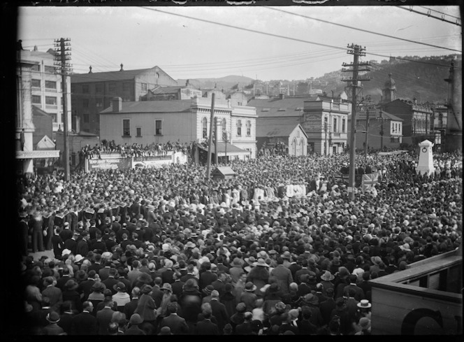 Crowd watching an ANZAC Day parade on Courtenay Place, Wellington. Shows people filling the street on either side of a thoroughfare to a War Memorial, and buildings in the background.