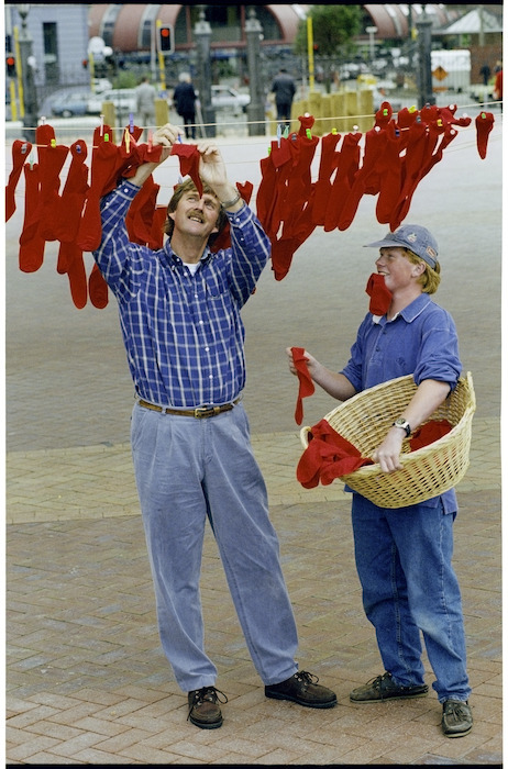 Sir Peter Blake and Philip Jameson hanging red socks on a clothes line - Photograph taken by Ross Giblin