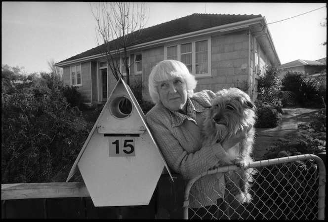 Mrs Zeta Tutt standing at the gate of her State house with her dog Benji, Naenae - Photograph taken by Phil Reid