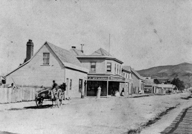 The corner of Cuba and Ghuznee Streets in the 1870s, showing the Kirkcaldie & Stains branch shop. 'Stains' can just be made out on the central building's verandah signage. This shop closed in 1876. Taken by an unidentified photographer. Ref: 1/2-031688-F