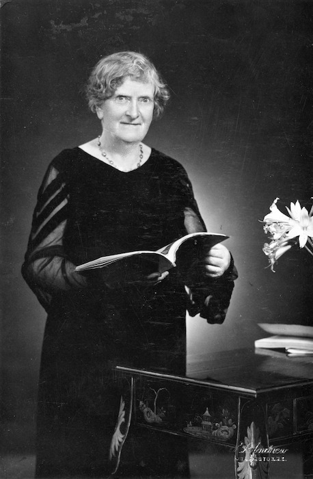 Black and white photo of Kate Anderson looking directly at the camera. She is wearing a long black dress and holds an open book above a side table with some flowers.