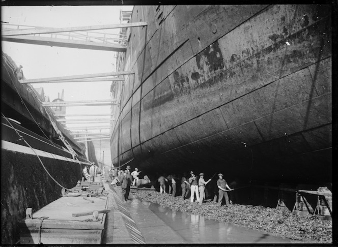 View of men working on the hull of a ship at an unidentified dry dock