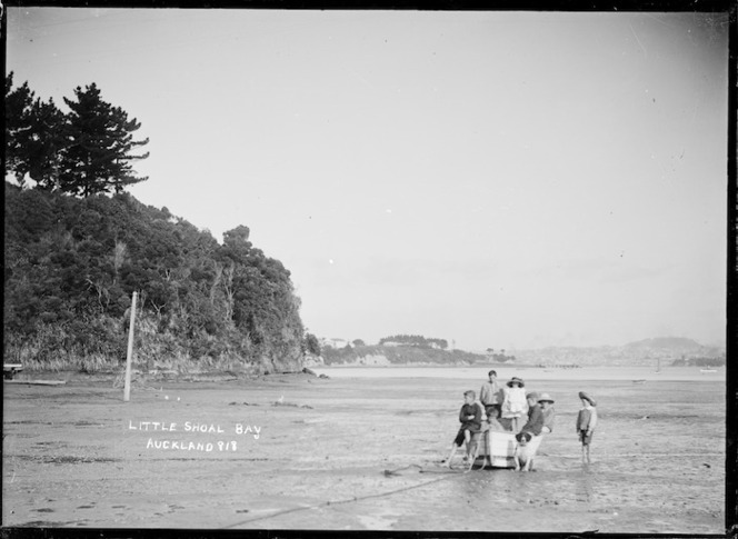 Children in a dinghy on the tidal flat, Little Shoal Bay, Auckland