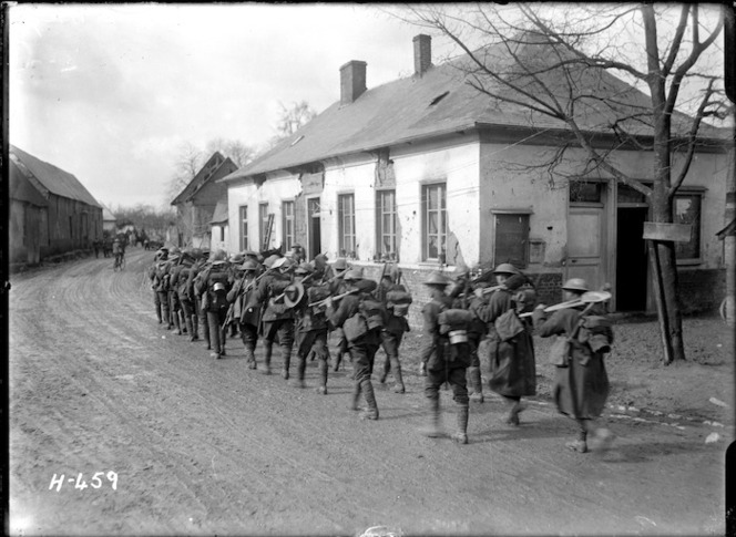A New Zealand working party walking through Courcelles, France, World War I.