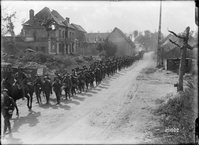 New Zealand troops marching though a residential area in France during World War l