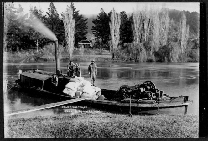Delivering stores in a barge on the Waikato River at Waipa, near Ngaruawahia, circa 1910
