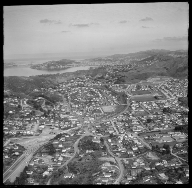 View over the Wellington City northern suburb of Johnsonville with the Southern Motorway under construction, Johnsonville Railway Station and Moorefield Road, to Wellington Harbour beyond