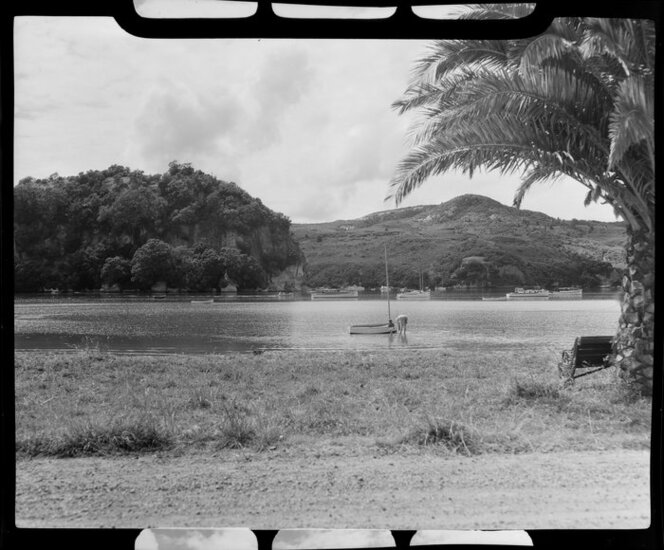 Unidentified woman and child paddling in the water beside a small sailing boat, Whitianga harbour