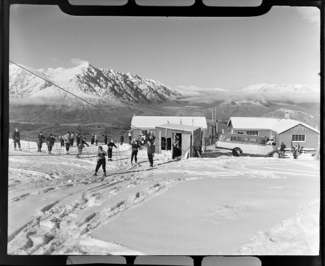 Skiing on Coronet Peak, Otago, showing chalet and ski lift. Whites Aviation Ltd :Photographs. Ref: WA-28982-F.