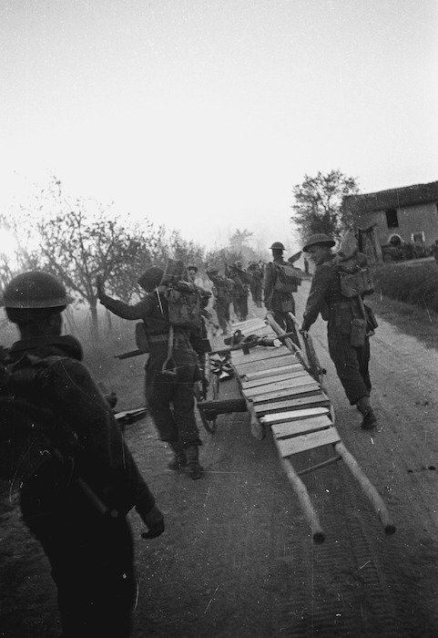 Kaye, George, 1914- : NZ infantrymen move forward at dusk with their bridging equipment to the Senio River, Italy