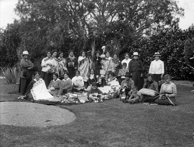Group of Māori women and children displaying handweaving on a lawn, in the shelter of a large tree
