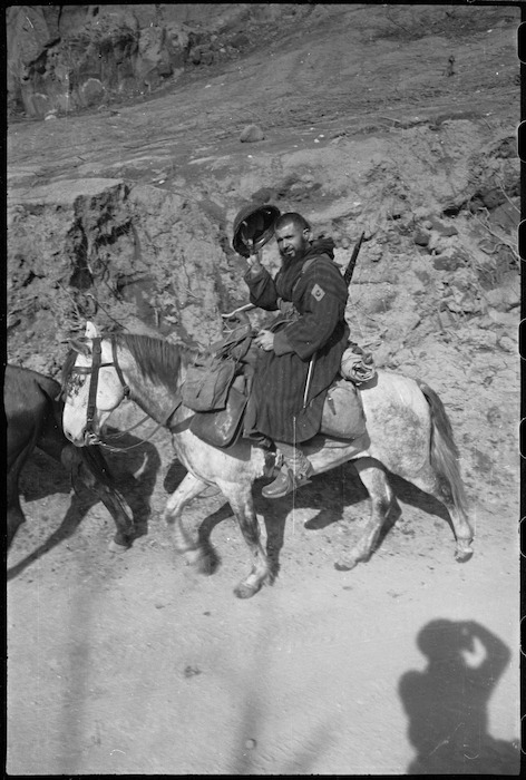 Mounted French Moroccan trooper raises steel helmet in greeting to New Zealanders on the Cassino Front in Italy, World War II - Photograph taken by George Kaye
