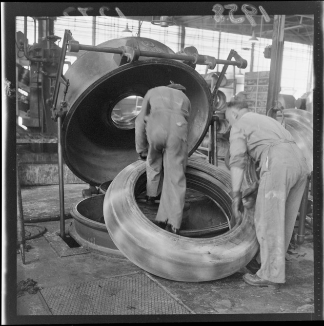 Unidentified workers fitting tyre on to press, Dunlop rubber factory, Upper Hutt