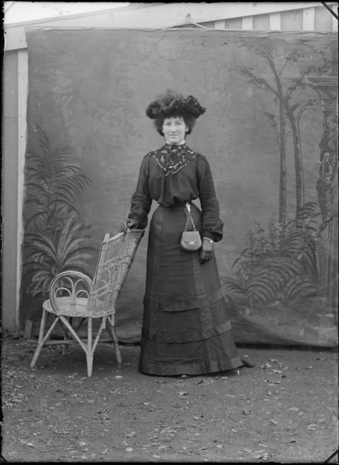 An unidentified woman in dark lace top dress, large hat, gloves and hip bag standing with cane chair.