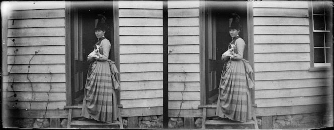 Stereograph of a woman in a small-bustled dress and a top hat, holding a dog.