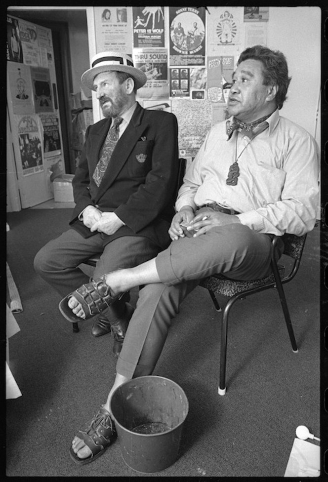 Poets Denis Glover and Hone Tuwhare, photographed in 1975, during a tour of 4 New Zealand poets, by an unidentified staff photographer for the Evening Post newspaper. Shows them seated in a room decorated with posters advertising live music shows. Hone Tuwhare has a tiki and a spotted handkerchief around his neck. He wears an open necked shirt, trousers and sandals. Denis Glover wears a suit and tie, with a straw boater.