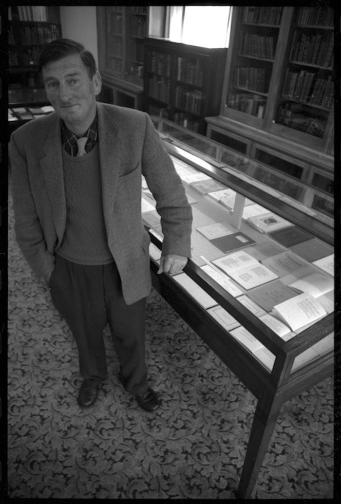 Denis Glover, the founder of Caxton Press, at the Alexander Turnbull Library with a Book Week display showing a selection of books produced by Caxton Press.