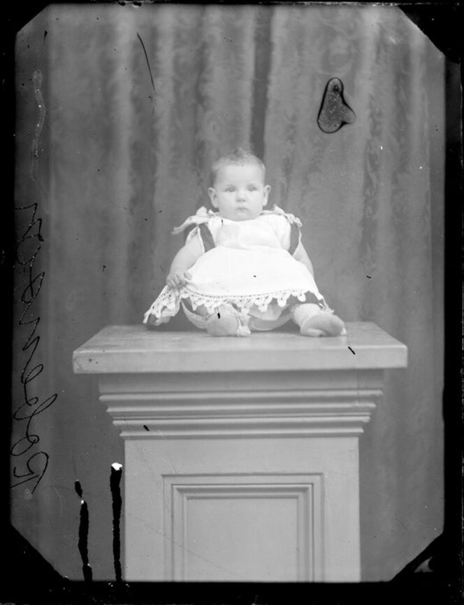 Baby Robinson sitting on a pillar.
