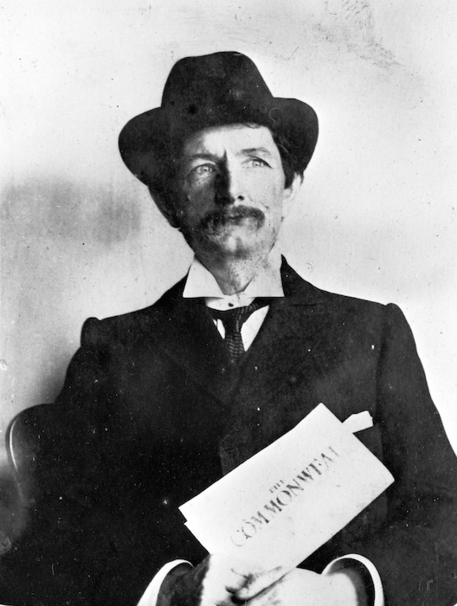 Robert Hogg, seated, wearing a hat and holding a copy of the socialist newspaper Commonweal.