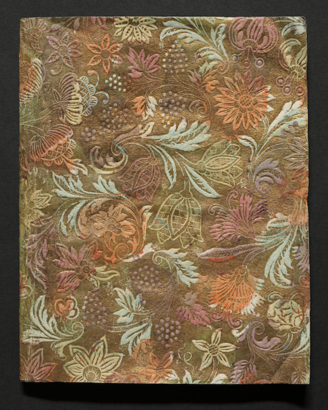 Colourful gilt endpaper, showing flowers, bunches of grapes, and leaves.