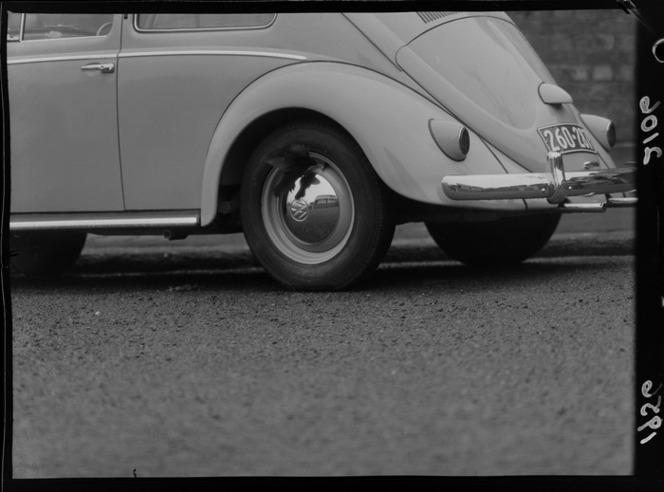 Blackbird pecking at hubcap of Volkswagon car