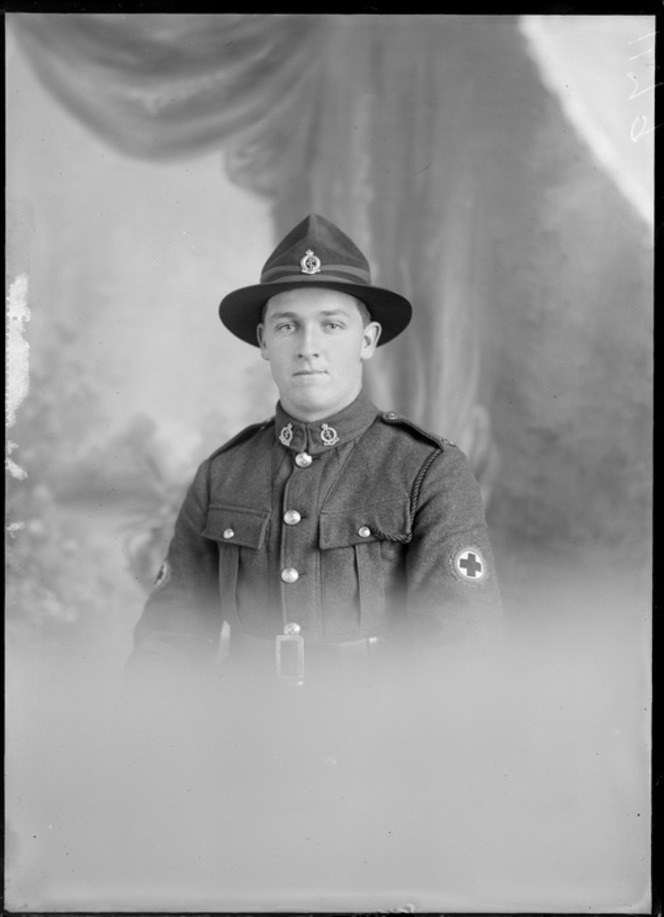Studio upper torso portrait of an unidentified man dressed in a Medical Corps army uniform, showing the Red Cross badge on his left upper arm, with two badges on the lapels of his jacket, with a pin on his hat, possibly Christchurch district. Maclay, Adam Henry Pearson, 1873-1955, Negatives. Ref: 1/2-163590-G