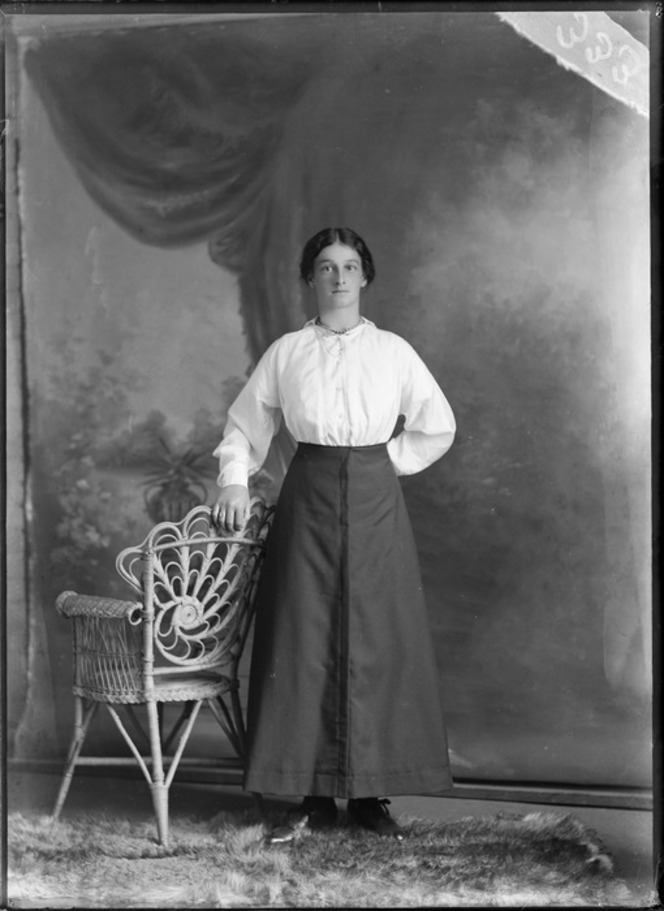 Studio unidentified portrait of a young woman in a cotton blouse and dark skirt with a pearl necklace and pin brooch.