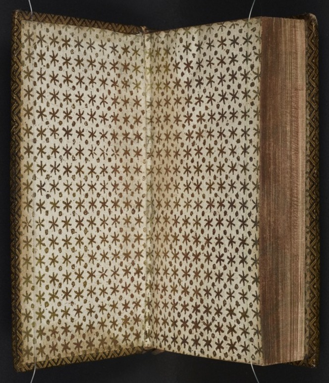 Endpaper with a regular gilt simple star and dot pattern