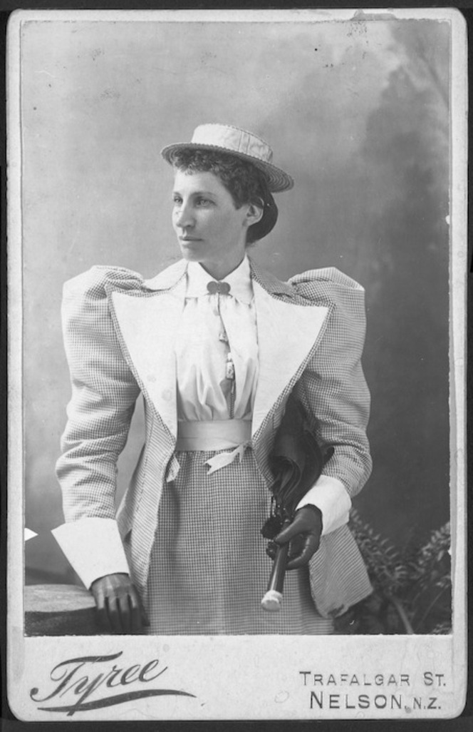 Studio portrait of a woman with very large sleeves and a small boater-like hat.