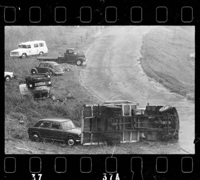 This photograph and the following one show how severe the cyclone was on land. Automobiles overturned by Wahine storm, Wellington. Dominion post (Newspaper) :Photographic negatives and prints of the Evening Post and Dominion newspapers. Ref: EP/1968/1581-F