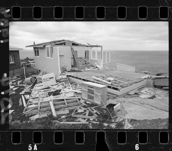 """House in Island Bay, Wellington, damaged by Wahine storm. Evening Post and Dominion newspapers. Ref: EP/1968/2014-F. Alexander Turnbull Library, Wellington, New Zealand. https://natlib.govt.nz/records/22474290. This photograph was taken a month after the cyclone. The caption from the paper reads """"Family forced to leave this ex-house"""". """"Perched on a bluff above Island Bay, this house is just one of the reminders in the city of last month's storm"""". """"Eventually the house will be repaired but in the meantime the wind and rain attack and erode what remains of the new home"""". 11 May. P21"""