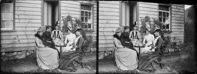 Stereograph of women having tea.Their upper garments are very tightly fitting, and their hats are a wonder to behold