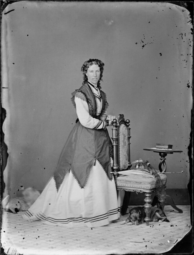 Woman standing for a portrait, not wearing crinoline.