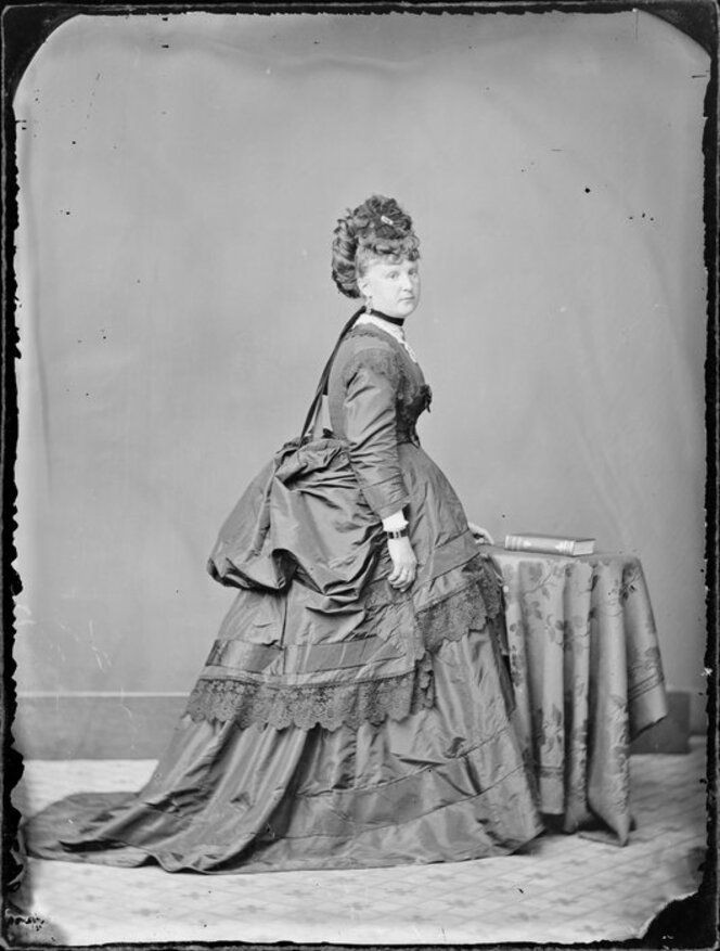 Woman in full bustle, overskirt, and tiny hat.