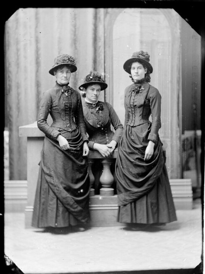 Three women without bustles, but with broad-brimmed hats.