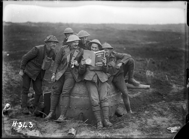 A group of soldiers from the 3rd Battalion, NZ Rifle Brigade, enjoy the joke of reading a copy of the publication 'New Zealand at the Front' while seated on a captured German anti-tank gun.