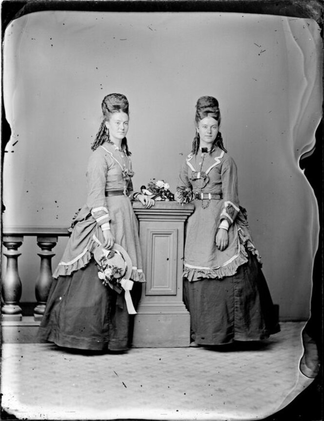 Two unidentified young women, wearing matching full length skirts and elaborate overdresses, with identical hairstyles, featuring ringlets and padded upswept hair.