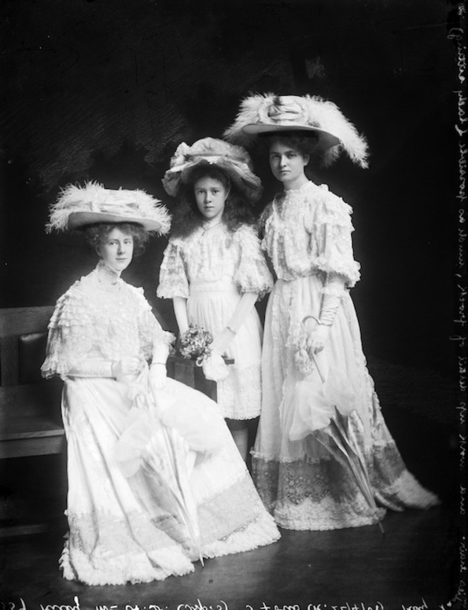 Three young women dressed in lace and hats. Big, feathery hats.