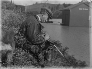 Image: [A man sitting on a bank beside a flooded area writing something]
