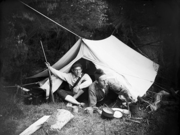 Image: L H Duval and William Williams sitting outside a tent with a gun, camera and other equipment