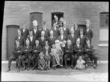 Image: Unidentified group, wearing party hats, outside a brick building, probably Christchurch district, includes man dressed up as Santa Claus holding balloons, with a small child sitting on his lap