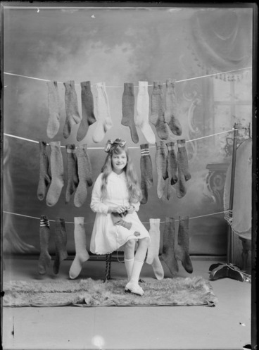 Image: Studio portrait of an unidentified girl sitting on a wooden stool knitting a sock, with three rows of socks hanging behind her, possibly Christchurch district