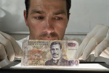 Image: Detective Constable Tim Crawford with fake $50 note - Photograph taken by Ross Giblin