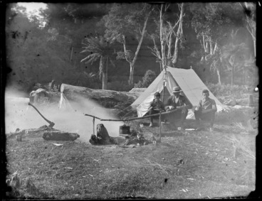 Image: Edgar and Owen Williams with unidentified man sitting outside a tent and eating a meal with the campfire in front, Catlins District