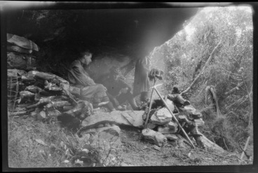 Image: Edgar Williams and an unidentified man, sitting by a campfire under a rock overhang, [Franz Josef, Westland District?]